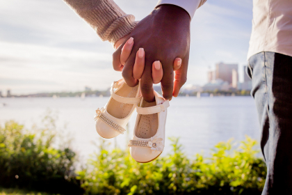 A man and woman hold hands in the sunshine. Intertwined in their hands are tiny baby shoes.