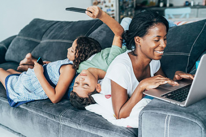 A young Black mother works on a laptop on her couch. Two children lay across her back, looking at their phones.