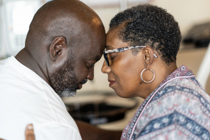 Sandra Davis-Quinney and her husband share a moment of contemplation, resting their foreheads on one another.