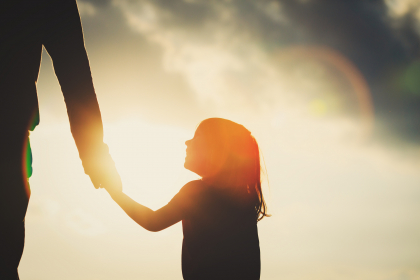 A girl holds and adult's hand, silhouetted by a sun in a cloudy sky.