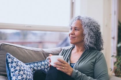 An older Hawaiian woman sitting on a couch holding a cup of coffee and looking into the distance