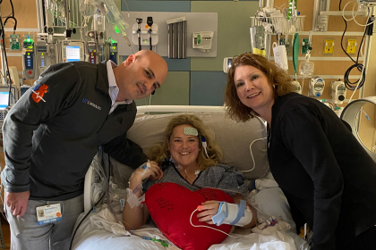 Heather Lowery laying in her hospital bed with Diego Moguillansky, MD, and Jana Reid, APRN, standing beside her.