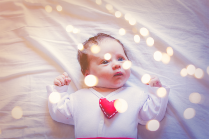A baby looking up at lights, wearing a jumper with a felt heart on it.
