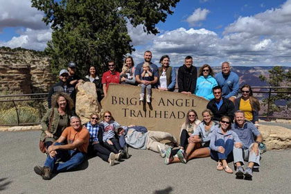 group of people around a sign that says bright angel trailhead