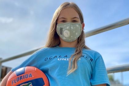 Kendall Lewis stands next to a volleyball net on a sunny day. She is wearing a face mask and is carrying an orange and blue Florida Gators volleyball.