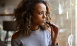 A curly-haried, dark-skinned young woman looks out a window while holding an e-cigarette to her lips.