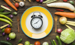 Stock image picturing an old-fashioned alarm clock centered on a plate and surrounded by vegetables