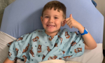 Baylor Bennett wearing a hospital gown tucked into a hospital bed smiling and giving a thumbs up