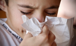 Boy sneezing into a tissue