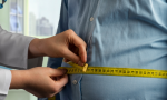 Stock photo: a physician encircles a man's midsection with a tape measure