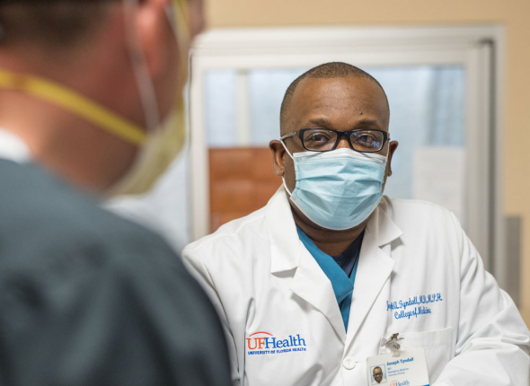 Dr. Adrian Tyndall, wearing mask, talks to another Uf Health caregiver