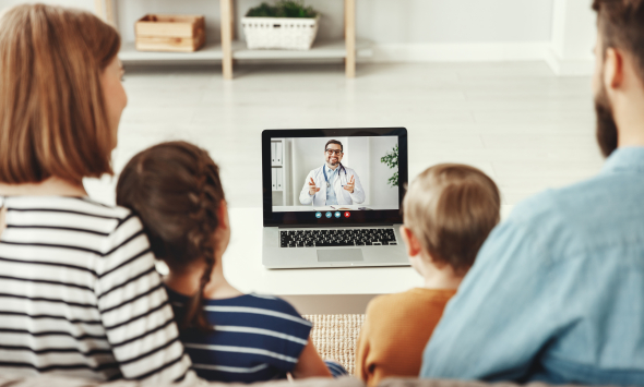 A mother, father, son and daughter face a computer talking to a male doctor using a video conferencing application.