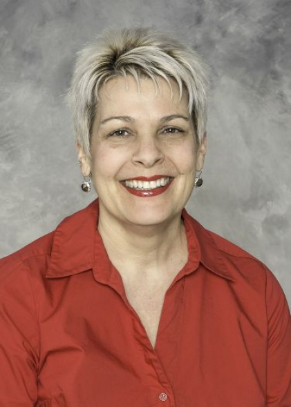 Dr. Julie Moore, Ph.D. smiles wearing a bright red collared shirt