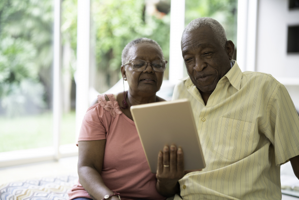 A older couple looks at a tablet while sitting in their home.