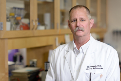 Mark Brantly, MD, stands in a lab facing the camera