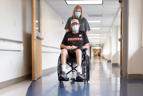 Melissa Buchanan pushing her husband on a wheelchair in a hallway.