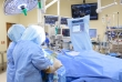 Larry D. Waldrop, M.D., on the right, and a surgical technician work during the opening minutes of a May 31 shoulder replacement surgery for Mercia Reid, 74, a Gainesville woman with severe arthritis. The surgery involved a new technology allowing computer-assisted navigation of the patient's shoulder using CT scan images.