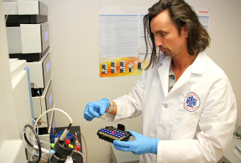 Researcher handles test vials for study.