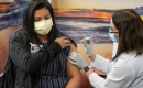 Emily Benitez lifts the sleeve of her outfit to receive an injection of the Moderna COVID-19 vaccine. A woman wearing a white medical coat provides the injection. Both are wearing masks.