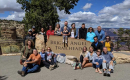 large group of people posing with a sign that says bright angel trailhead
