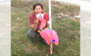 A woman crouching down on the ground posing with a flamingo figurine wearing a santa hat