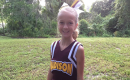 madison standing outside and smiling at the camera in a cheerleading uniform