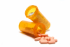 Orange plastic pill bottles with pills.