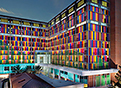 The outside of UF Health Shands Children's Hospital is lit up during the twilight of sunlight. The blue, red, yellow and purple panels that make up its outside seem to glow.